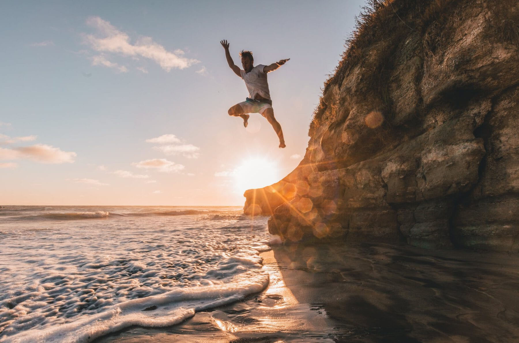 man jumps from cliff to water