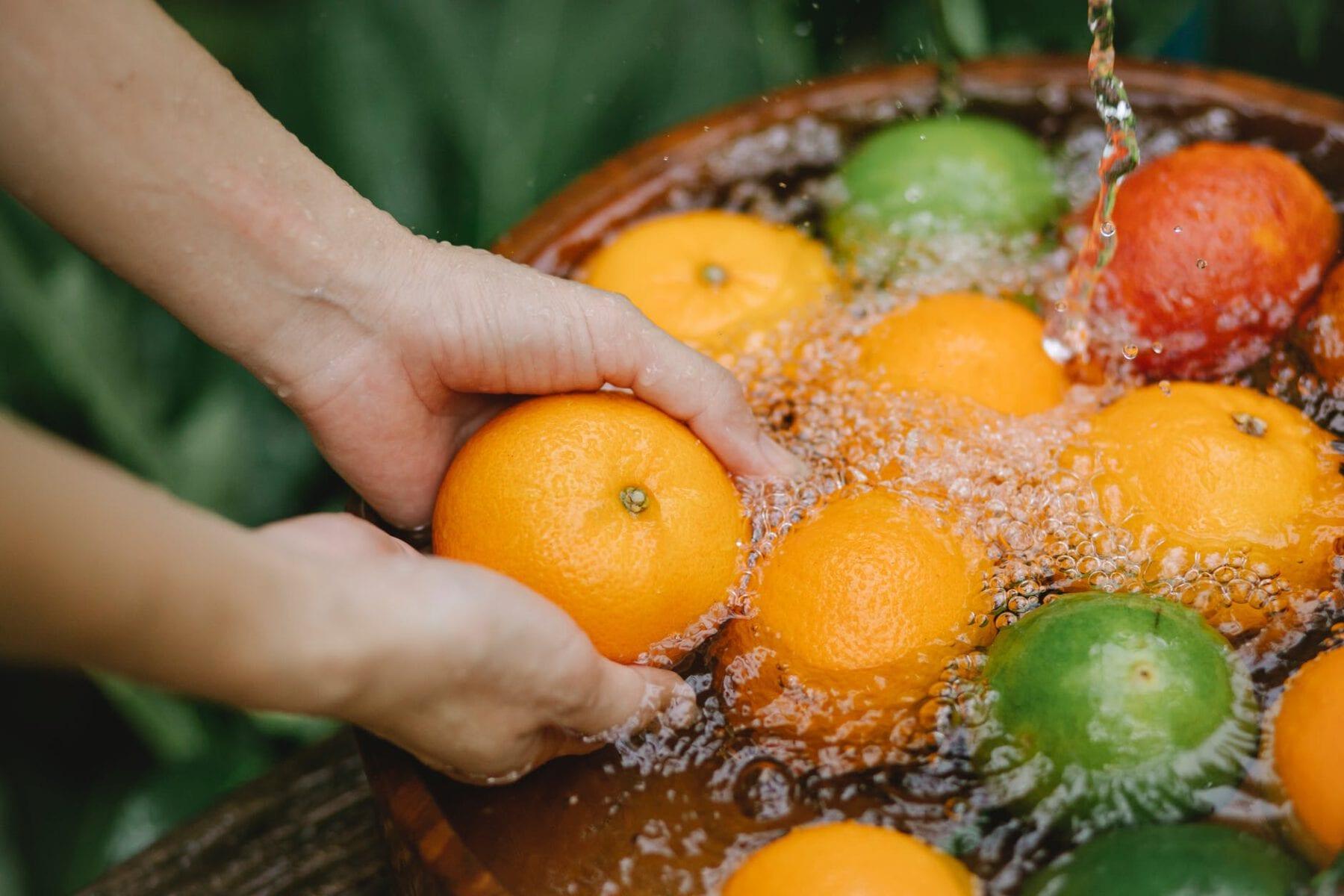 woman washing fruits in fresh water