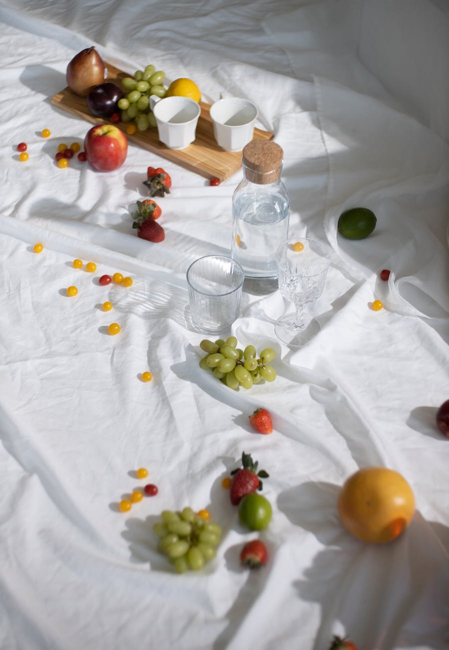 fresh fruits with grape arranged with glassware